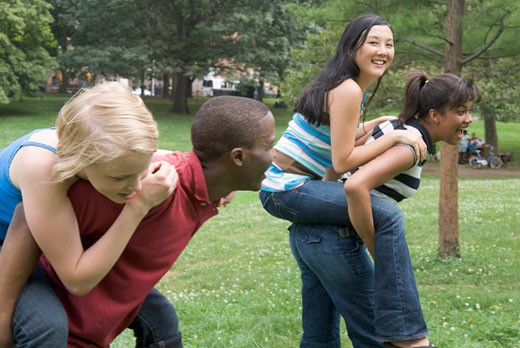 Stock Photo: 1779R-20552 Group of teenagers giving piggy back rides outdoors