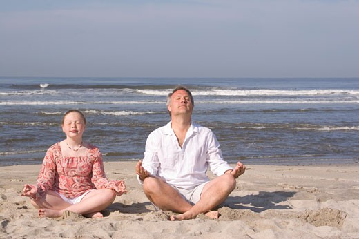 Stock Photo: 1779R-20667 Father and daughter meditating on beach