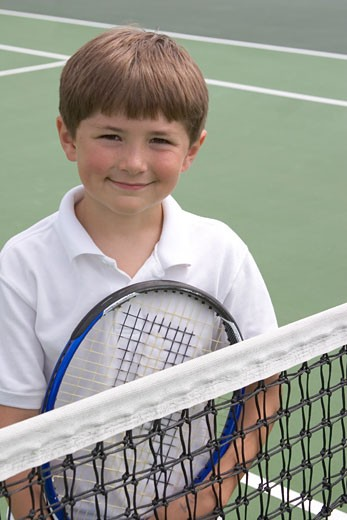 Young boy playing tennis : Stock Photo