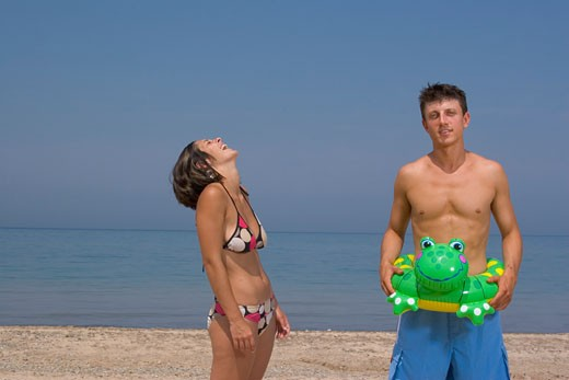 Young couple laughing on beach : Stock Photo