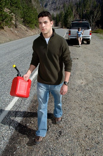 Man carrying gas can : Stock Photo