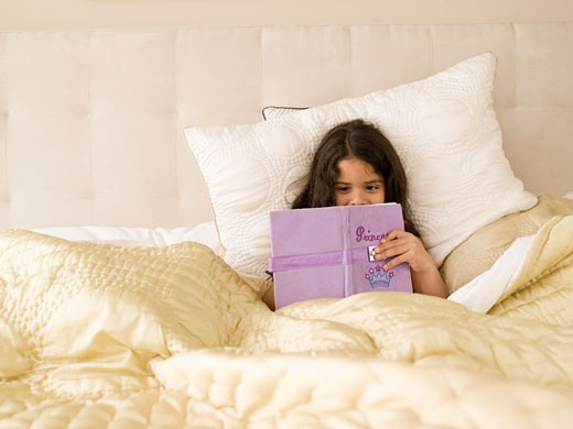 Girl writing in diary in bed : Stock Photo