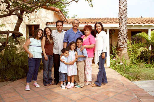 Extended Hispanic family standing in front of house : Stock Photo