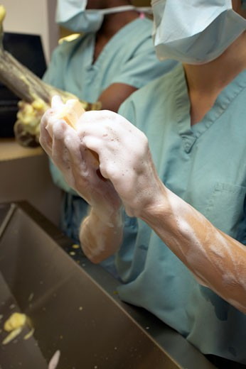 Surgeons washing their hands before surgery : Stock Photo