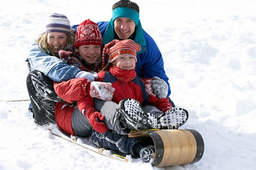 Family sledding down snowy hill : Stock Photo