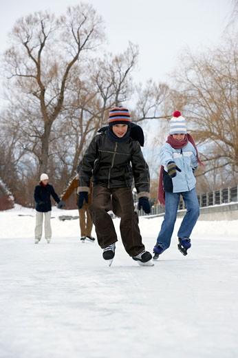 Children having ice skating race : Stock Photo