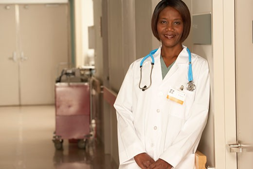 Female doctor standing in corridor : Stock Photo