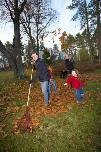 Family raking leaves : Stock Photo