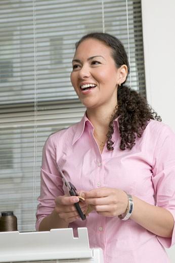 Hispanic woman cutting pieces of fabric : Stock Photo