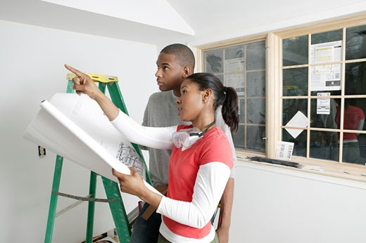 African couple discussing plants for unfinished room : Stock Photo