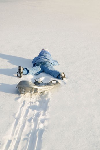 Child falling off sled in snow : Stock Photo