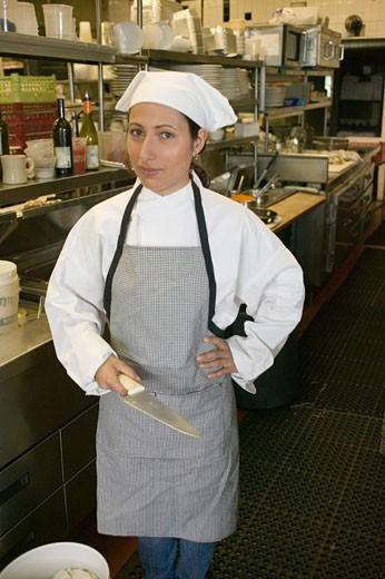 Hispanic female chef holding knife in kitchen : Stock Photo
