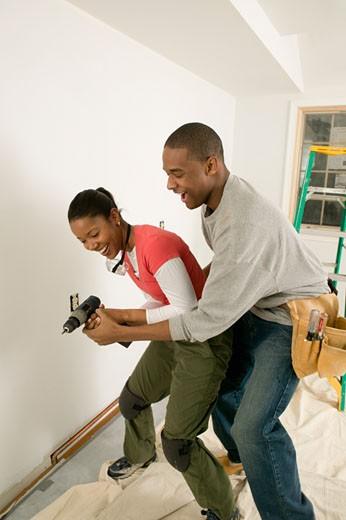 Male carpenter wrestling power drill away from girlfriend : Stock Photo