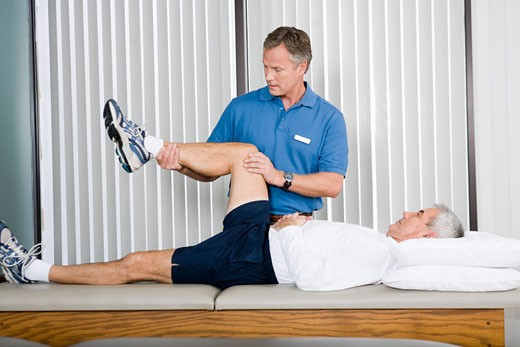 Physical therapist stretching man's leg : Stock Photo
