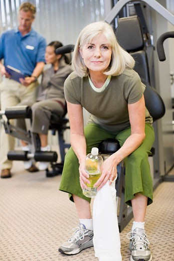 Senior woman sitting on exercise machine : Stock Photo
