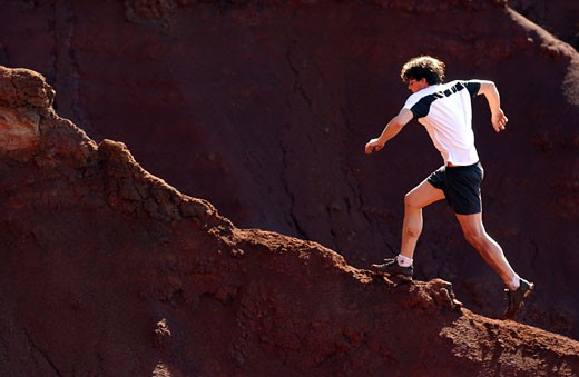 Young man running along cliff wall : Stock Photo
