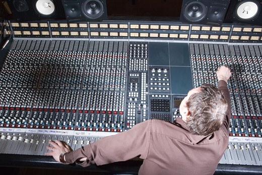 Producer adjusting sound equipment : Stock Photo