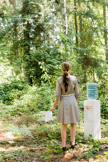 Businesswoman next to water cooler in woods : Stock Photo
