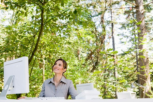 Stock Photo: 1779R-23210 Businesswoman at desk in woods