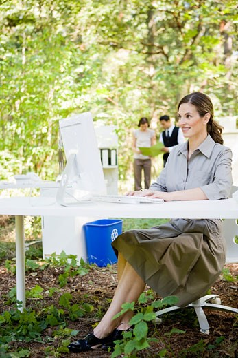 Businesswoman at desk in woods : Stock Photo