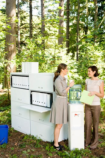 Businesswomen talking at water cooler in woods : Stock Photo