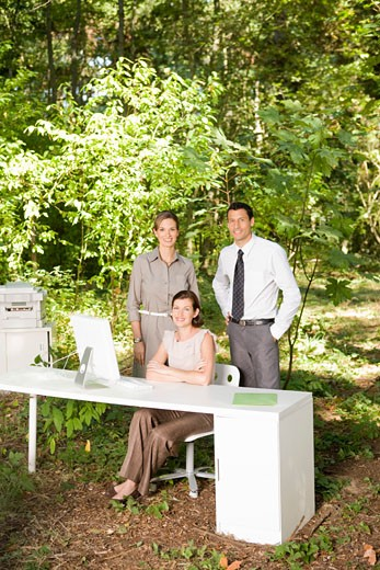 Businesspeople next to desk in woods : Stock Photo