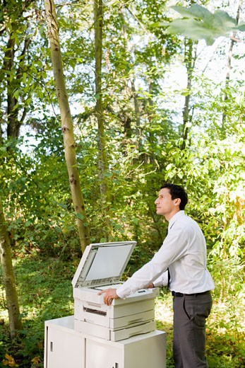 Businessman leaning on copier in woods : Stock Photo