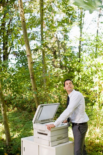Stock Photo: 1779R-23221 Businessman leaning on copier in woods