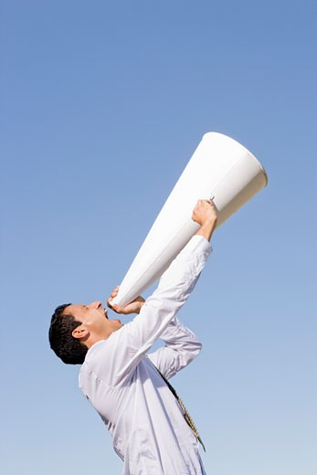 Businessman yelling through megaphone : Stock Photo