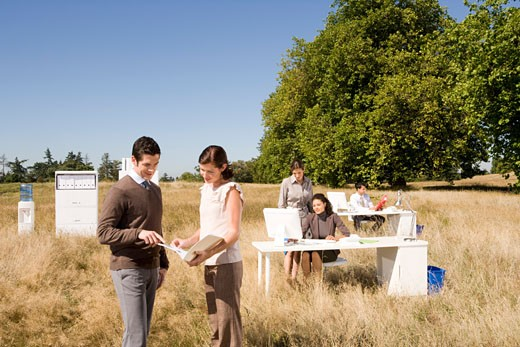 Businesspeople looking at paperwork in field : Stock Photo