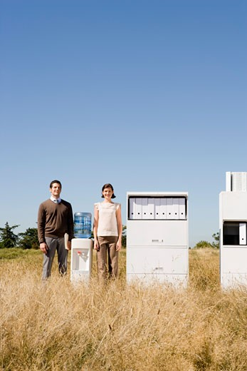 Stock Photo: 1779R-23237 Businesspeople next to water cooler in field