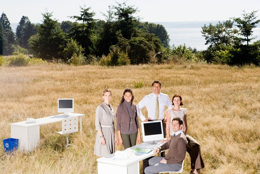 Businesspeople around desk in field : Stock Photo