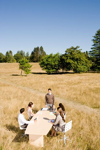 Stock Photo: 1779R-23247 Businesspeople at conference table in field