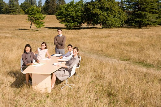 Businesspeople at conference table in field : Stock Photo