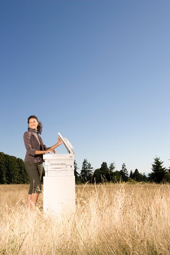 Businesswoman next to copier in field : Stock Photo