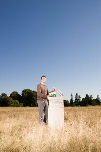 Businessman next to copier in field : Stock Photo