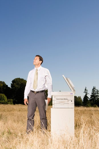 Businessman next to copier in field : Stock Photo