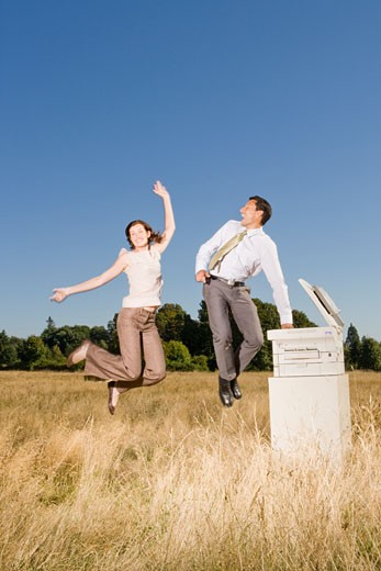 Businesspeople jumping next to copier : Stock Photo