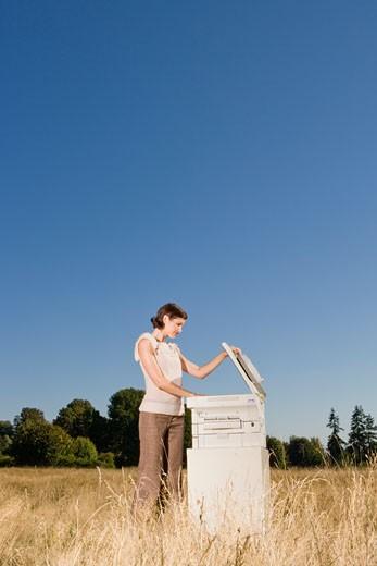 Businesswoman next to copier in field : Stock Photo
