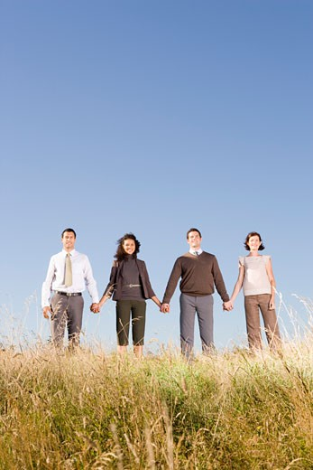 Businesspeople holding hands in field : Stock Photo
