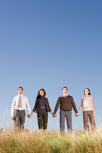 Stock Photo: 1779R-23268 Businesspeople holding hands in field