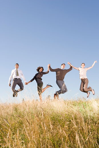 Stock Photo: 1779R-23271 Businesspeople jumping in field