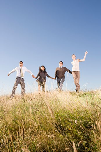 Stock Photo: 1779R-23272 Businesspeople skipping in field