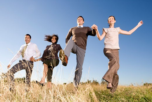 Businesspeople skipping in field : Stock Photo