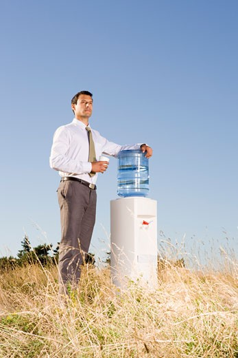 Businessman next to water cooler in field : Stock Photo