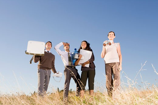 Businesspeople holding office supplies in field : Stock Photo