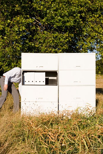 Businessman with head behind file cabinet : Stock Photo