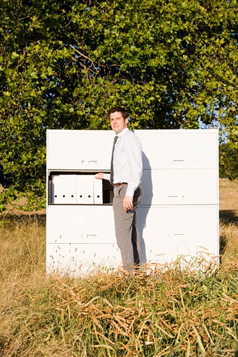 Businessman next to file cabinet in field : Stock Photo