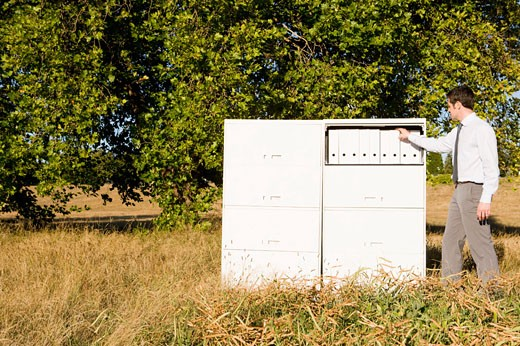 Stock Photo: 1779R-23288 Businessman next to file cabinet in field