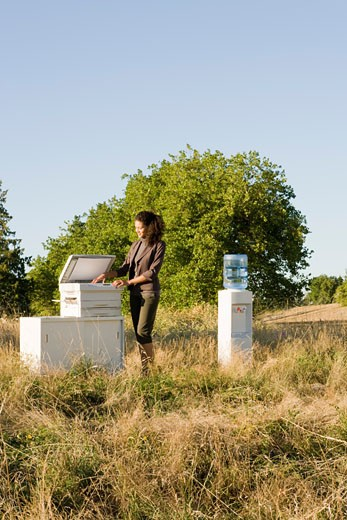 Stock Photo: 1779R-23291 Businesswoman next to copier in field